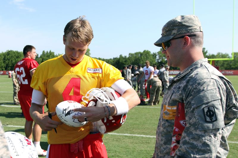 Chiefs playing singing a football for Kansas National Guardsman