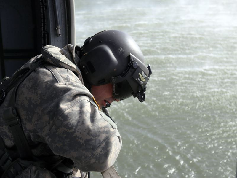 Sgt. T.L. Dickey observes the Bambi bucket suspended below a Kansas National Guard Black Hawk helicopter